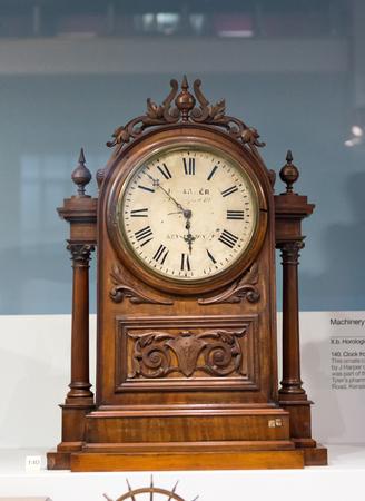 Één houten antieke klok met sierlijke gravure gedecoreerd, tentoongesteld in glazen kast