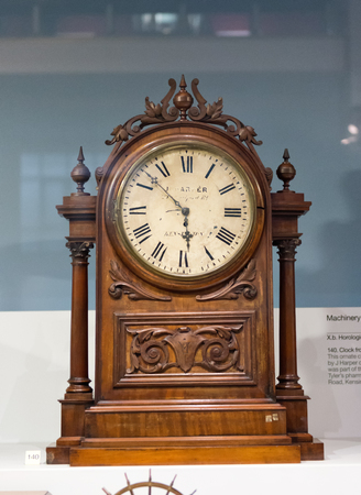 Single wooden antique clock with ornate carving decoratation on display inside glass case