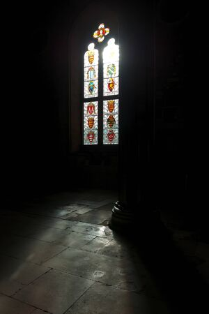 stained glass windows: Bright sunlight pouring through stained glass windows in dark room of old medieval era Winchester castle in Britain