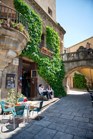 historical building: Couple Enjoying Coffee on Cafe Patio - Sunny Patio Outside of Ivy Covered Historical Building in Poble Espanyol District, Barcelona, Spain