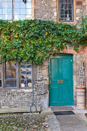 green door: Colorful turquoise blue wooden entrance door in an old stone building with a green creeper trailing over the wall
