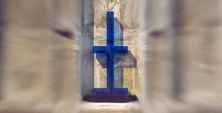 messiah: Colorful blue cross against an old stone wall with ornate carvings inside a church or cathedral Stock Photo