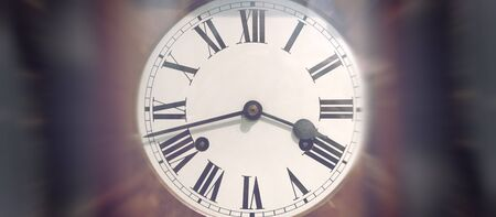 temporal: Simple antique wind up clock face with Roman numerals and dark blurry edges Stock Photo