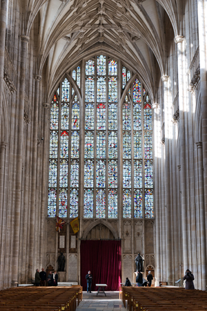 winchester: WINCHESTER, UK - FEBRUARY 07: The nave looking towards the West Windows stained glass mosaic inside Winchester Cathedral. February 07, 2016 in Winchester, UK