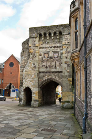 winchester: Distant person walking on stone street through arch at old medieval building in Winchester, United Kingdom Stock Photo