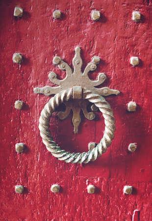 knocker: Old metal door knocker closeup in front of red wooden door