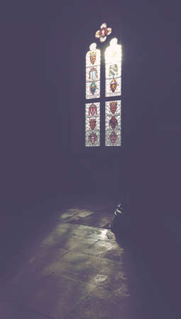 winchester: Bright sunlight showing through stained glass windows in old medieval era Winchester castle in Britain