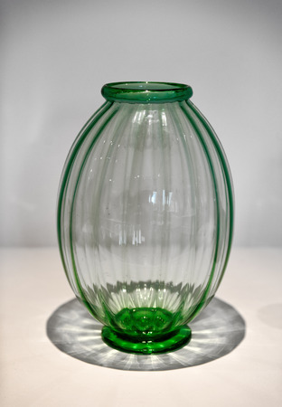 Attractive modern ribbed green glass vase throwing an interesting shadow at the foot , Murano, Venice, Italy, famous for its glass blowing