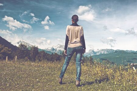admiring: Woman standing admiring the alpine view in the Berchtesgaden National Park in Germany looking out over snow-capped peaks