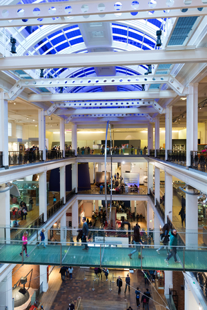view of an atrium in a building: Interior entrance hall of the Science Museum, London looking down the length of the hall from above showing the crowds of people on each level