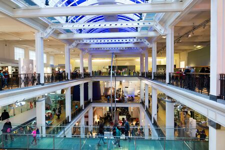 view of an atrium in a building: Crowds of people in the Science Museum in London with a view down the entrance hall of the three floors of the building and atrium Editorial