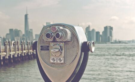 city view: Close Up of Scenic Binoculars with View of New York City Skyline in Background, as seen from Pier of Liberty Island, New York, USA