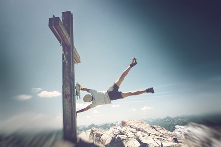 summits: Humorous Image of Man Clinging to Summit Cross on Extremely Windy Day in Allgau Alps with View of Mountains in Background, on Sunny Day with Blue Sky