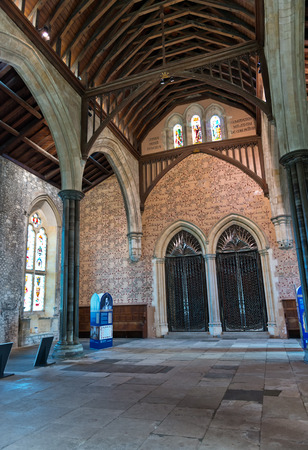 rafters: Interior of historic old English cathedral with slab stone floor and stained glass arched windows under wooden rafters