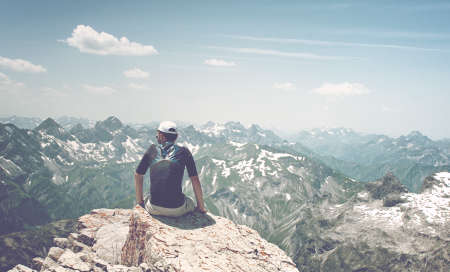 allgau: Man Sitting on Rock Ledge Enjoying the View and Serenity of Allgau Alps Mountain Ranges on Sunny Day with Blue Sky Stock Photo