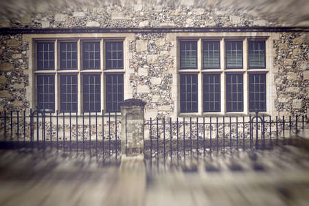 glass fence: Blurry edged view of eight old glass paned windows with stone walls and iron fence in front Stock Photo