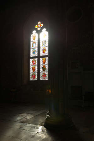 winchester: Bright sunlight pouring through stained glass windows in dark room of old medieval era Winchester castle in Britain