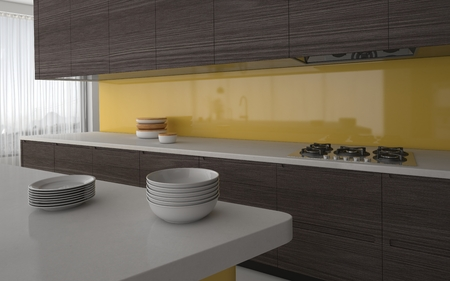 splash back: Modern kitchen with yellow splash back and grey cabinetry with a view past stacked plates to the electric hob. 3d Rendering. Stock Photo