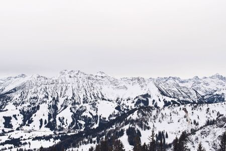 forested: Wide view under overcast sky and forested snow covered mountain range and foothills Stock Photo