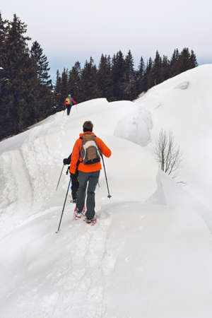 view from behind: Cross-country skier traversing a snowy mountain slope in alpine scenery in winter wearing a backpack, view from behind with a second person in the distance ahead