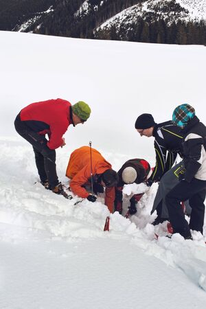 WERTACHER HOERNLE, WERTACH, GERMANY - FEBUARY 28 2016: Team of alpine rescuers digging in snow for a buried victim standing grouped around an excavated hole as they train using new techniques for rapid response