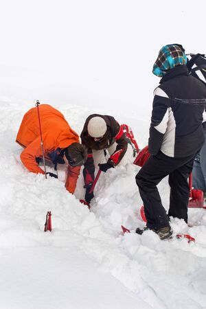 offpiste: WERTACHER HOERNLE, WERTACH, GERMANY - FEBUARY 28 2016: Team of Alpine search and rescue rescuers training to locate and rescue a person buried off-piste in snow digging below the surface with spades Editorial