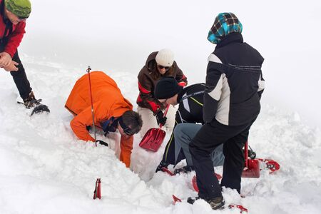 paramedics: WERTACHER HOERNLE, WERTACH, GERMANY - FEBUARY 28 2016: Team of paramedics and mountain rescuers digging for a victim buried in deep snow after locating a GPS signal