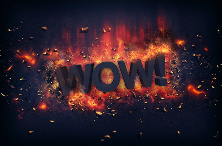 red hot iron: Burning orange fiery flames and explosive sparks on a dark background with the word - WOW ! - in black text for a dramatic poster design