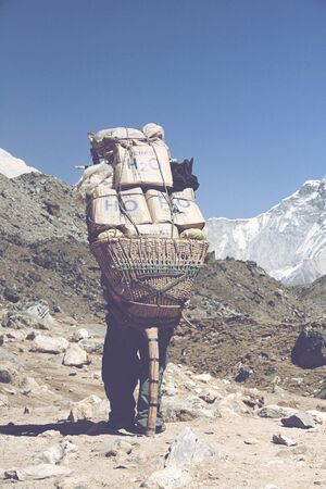 oxigen: GORAK SHEP, NEPAL - CIRCA MARCH 2010: Rear view of single sherpa tourism guide carrying large bundel of supplies surrounded by rocks and mountains