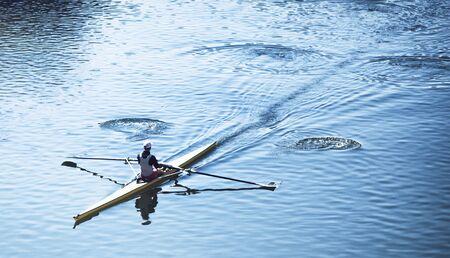 bateau de course: High angle de vue d'une personne godille dans un canot de course sur l'eau calme déplaçant en diagonale à travers le cadre, avec copie espace