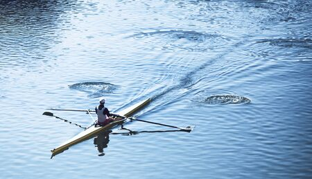 High angle view of a person sculling in a racing canoe on calm water moving diagonally through the frame with copy space