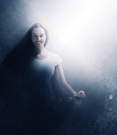 evocative: Smiling woman meditating in a glow of light emanating from the side through textured misty shadows in an evocative portrait
