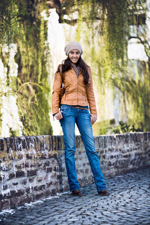 full willow: Full Length Portrait of Attractive Young Indian Girl Wearing Leather Jacket and Cap Smiling and Standing with Hands in Pockets on Cobblestone Bridge in Urban Setting with Willow Trees Stock Photo