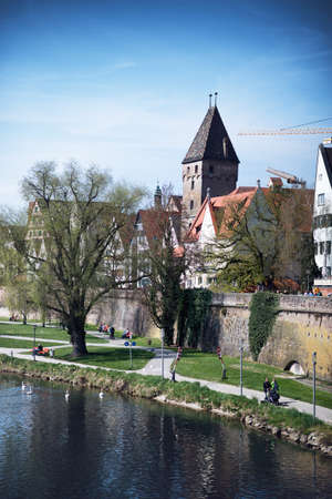 walking paths: Tranquil Scenic of Walking Paths on Banks of River Blau in front of Walled City with View of Historical Metzgerturm Butcher Tower on Sunny Spring Day with Blue Vignette Sky Editorial