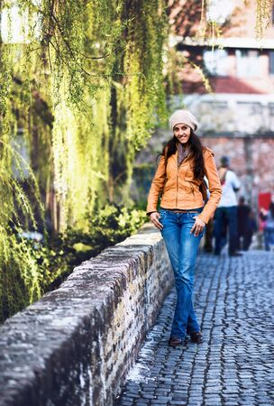 nonchalant: Full Length Portrait of Attractive Young Indian Girl Wearing Leather Jacket and Cap Smiling and Standing with Hands in Pockets on Cobblestone Bridge in Urban Setting with Willow Trees Stock Photo