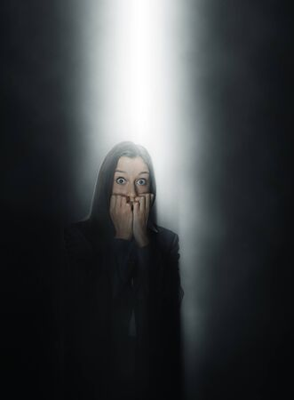 angst: Petrified woman standing in a beam of light shining from above through the darkness with wide staring eyes biting her nails in fear Stock Photo