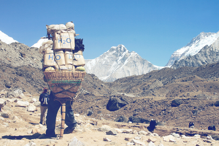 oxigen: GORAK SHEP, NEPAL - CIRCA MARCH 2010: Sherpa carrying a large load on his back as he carries provisions for a mountaineer during a trekking expedition in Nepal with a view of the Himalayas Editorial