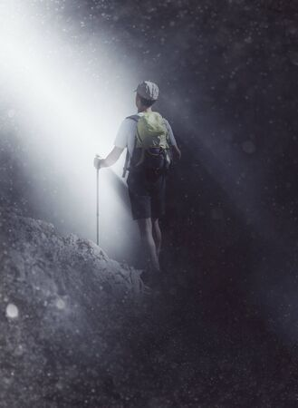 darkness: Mountaineer or hiker trekking up a steep slope walking towards a beam of light shining down through the misty darkness