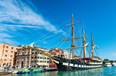 italian architecture: The Palinuro, a historic Italian navy training barquentine, moored in Venice Italy in the Giudecca Canal in front of historic the colorful architecture of the city Editorial
