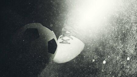 campeonato de futbol: Rayo de luz que ilumina una bota de fútbol y la bola con una capa de textura grunge Foto de archivo