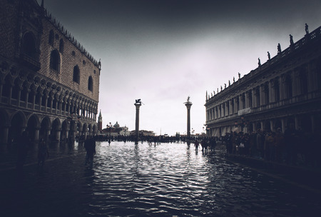 low angle views: VENICE, ITALY - 17 OCTOBER 2015: St. Marks Square (Piazza San Marco) during high tide (acqua alta) in Venice, Italy. Acqua alta is an unusual high tide, which floods parts of Venice. October 17 2015. Editorial