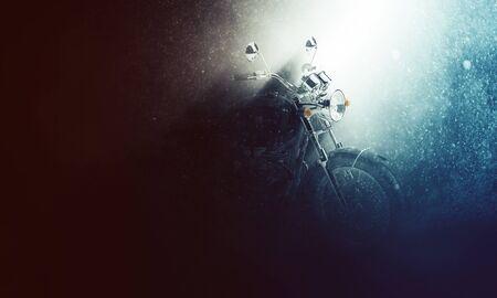 コピー スペースと、霧の深い闇の中にハンドルバーを照明する光のシャフトで雨嵐の雰囲気のバックライト付きのバイク 写真素材