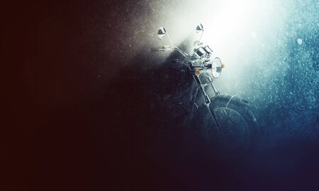 Motorbike in a rainy stormy atmosphere backlit by a shaft of light illuminating the handlebars in the misty darkness, with copy space