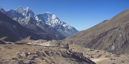 silt: Silt in dry valley of Himalayan foothills with high mountain peaks covered in snow under panoramic blue sky