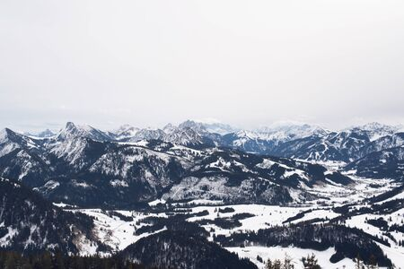 forested: Scenic panorama of steep alpine mountains and forested valleys in snow looking far into the distance across the ranges Stock Photo