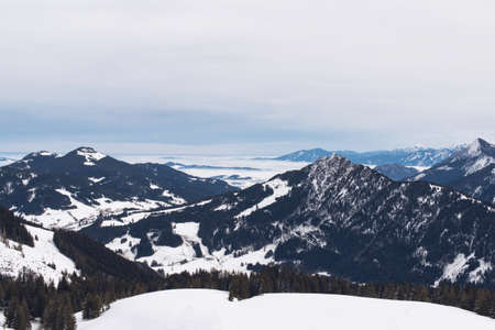 vast: View from atop ski hill of cloudy skies above vast snow covered mountain range and scattered evergreen forests