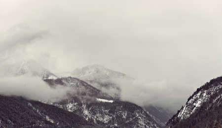 looming: Dark winter clouds looming over snow covered mountains partially covered by snow Stock Photo