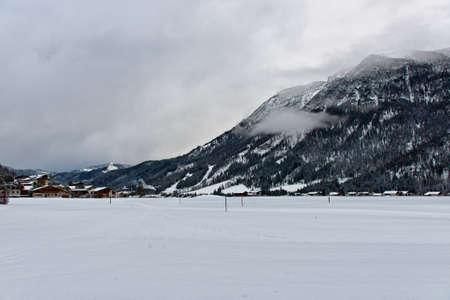 llanura: pueblo de la estación de esquí en Achenkirch, Austria sin mucha gente cerca de montaña nublado y hotel en el fondo