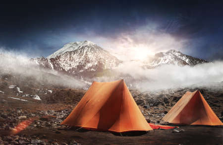 pitched: Two tents pitched below snow capped mountains at sunrise with a bright sunburst over the tops of the peaks and early morning mist clinging to the landscape