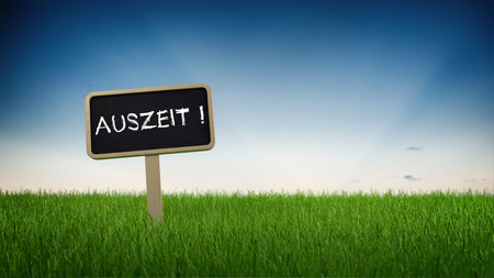 auszeit: Ground level perspective on German language time out sign stuck in green grass with clear blue sky background